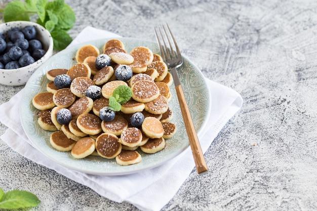 朝食用の小さなパンケーキ。灰色の背景のプレートにブルーベリーとシリアルのパンケーキ。