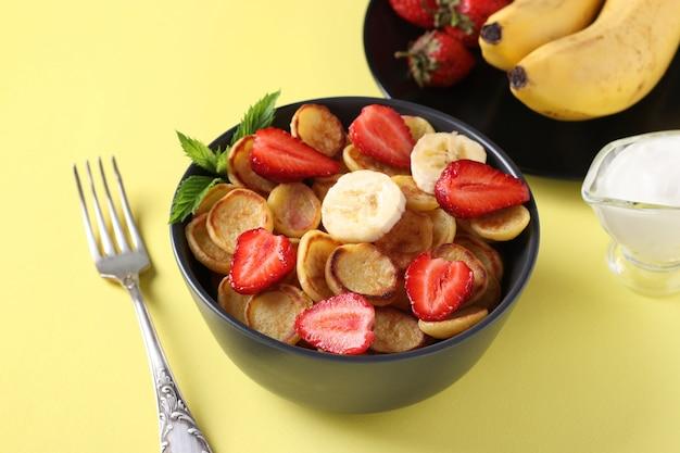 イチゴ、バナナ、サワークリームと朝食用の小さなパンケーキ