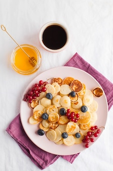 白いテーブルクロスとテキスト用のスペースにベリー、蜂蜜、コーヒーの小さなパンケーキ