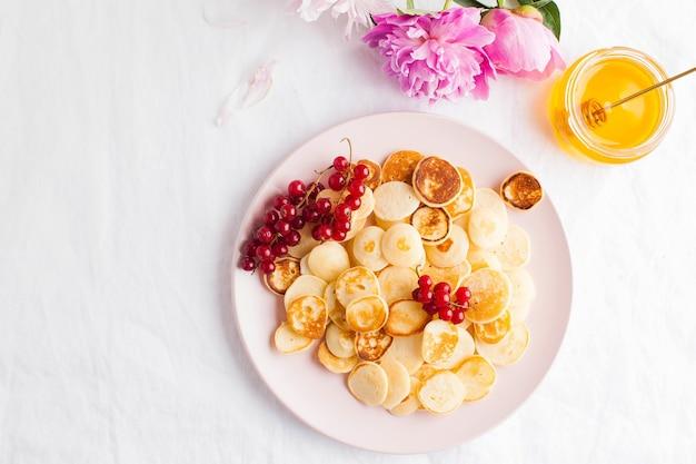 白いテーブルクロスとテキスト用のスペースにベリー、蜂蜜、花の小さなパンケーキ