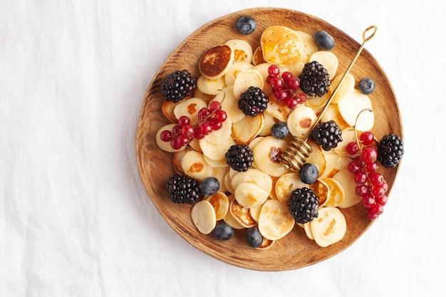 白いテーブルクロスのクローズアップでベリーと小さなパンケーキ