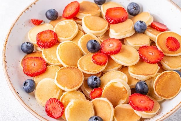 朝食にイチゴとブルーベリーの小さなパンケーキ。セレクティブフォーカス。