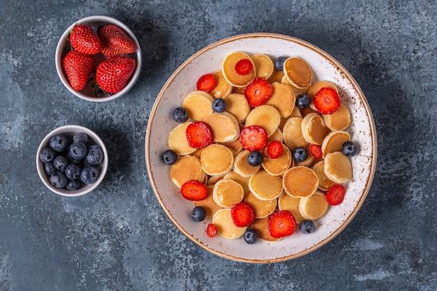 朝食にイチゴとブルーベリーの小さなパンケーキ。上面図。