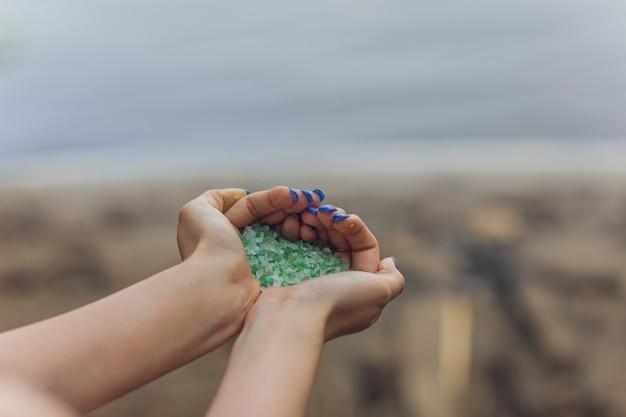 환경 주의자 마이크로 플라스틱의 손에 모래 해변에서 수집 된 작은 플라스틱 조각이 바다와 해양 생태계를 오염시키고 있습니다.
