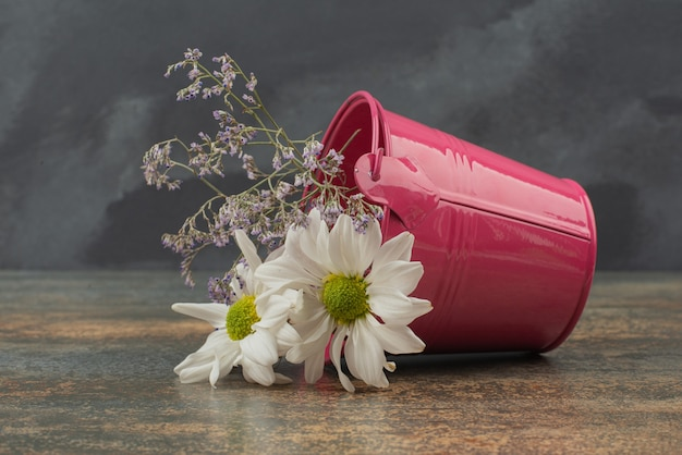 Tiny pink bucket with bouquet of flowers on marble surface.