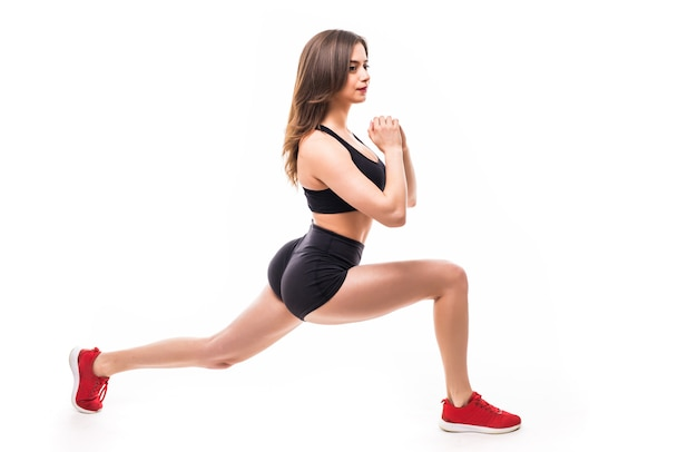 Tiny sport brunette sexy woman in black sportswear does exercises for strong figure body