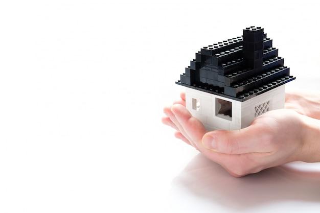 Tiny toy bricks house in hand