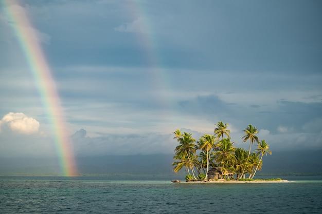 Крохотный тропический необитаемый островок в море с пальмами и радугой на пасмурном небе, отдых в ...
