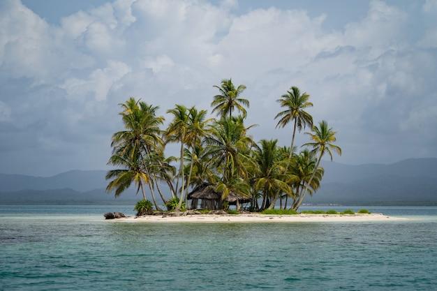Крошечный тропический необитаемый остров с кокосовыми пальмами и пляжем с белым песком для отдыха и путешествий ...