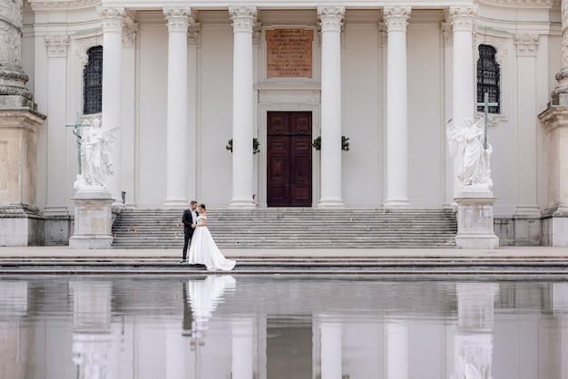 Tiny wedding couple is walking near the huge cathedral with white columns and reflection in the water