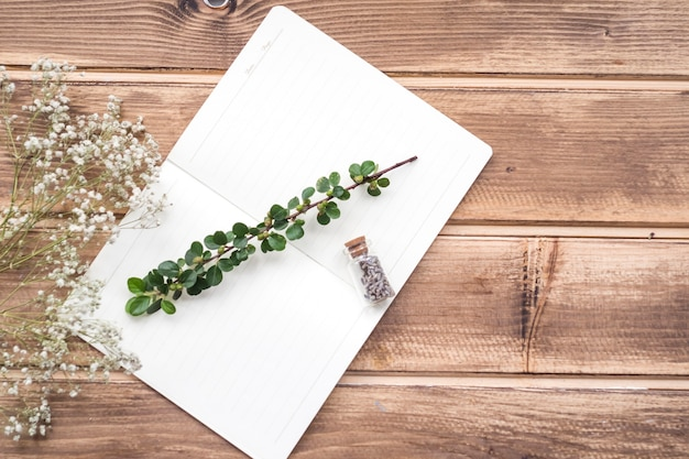 Tiny white flowers with stem and lavender flower bottle on notebook over the wooden backdrop