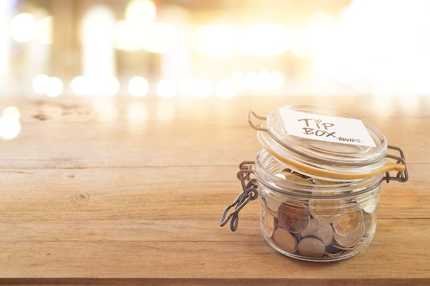 Tip box, coins in a glass jar in cafe front of mirror at night