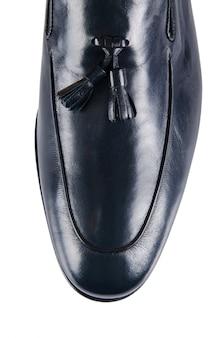 白で隔離される男性の靴の先端