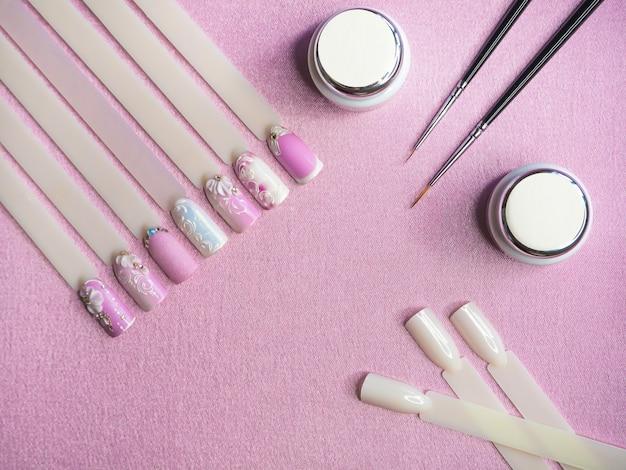 Советы и краска для рисования на ногтях на розовом фоне. креативная концепция маникюра.