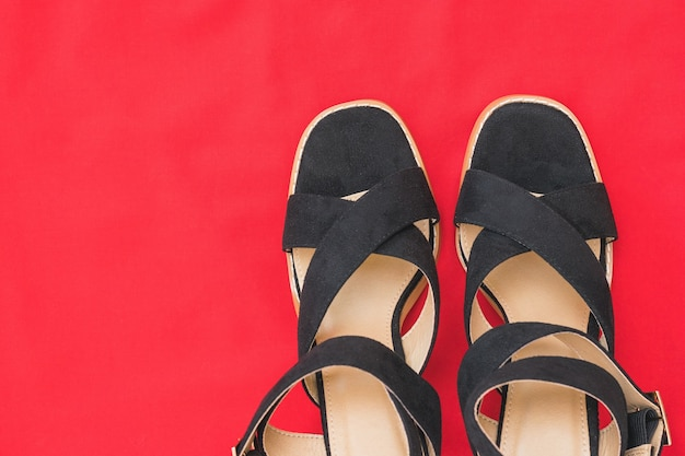 The tips of black women's fashionable shoes on a background of red fabric. fashionable women's shoes. flat lay.