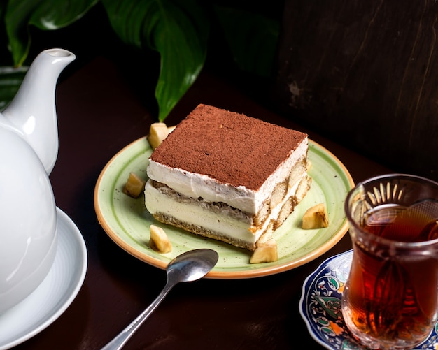 Tiramisu cake with cacao powder on top served with tea