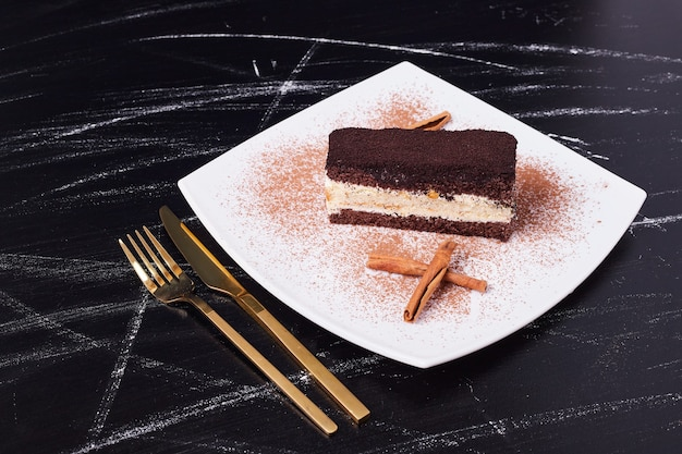 金色のカトラリーの横にある白いプレートにシナモンを添えたティラミスケーキ。