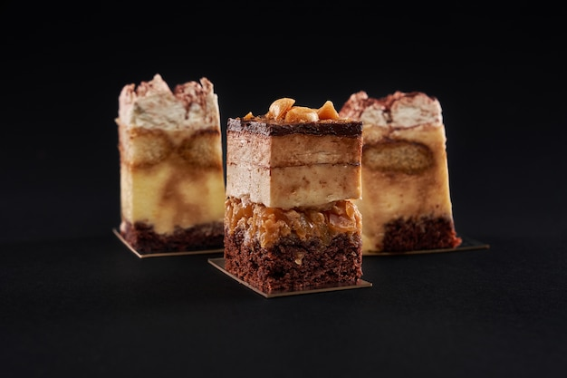 Tiramisu cake with three layers of chocolate biscuit and natural coffee syrup with cognac and cream. three square pieces in row decorated with whipped cream and cocoa, isolated on black wall.