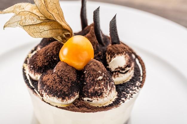 Tiramisu dessert cake with ground cherry closeup on white plate