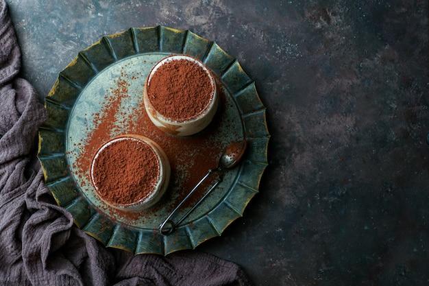 Tiramisu dessert in glasses on dark concrete