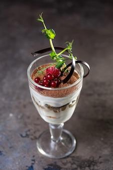 Десерт тирамису в стакане с ягодами.