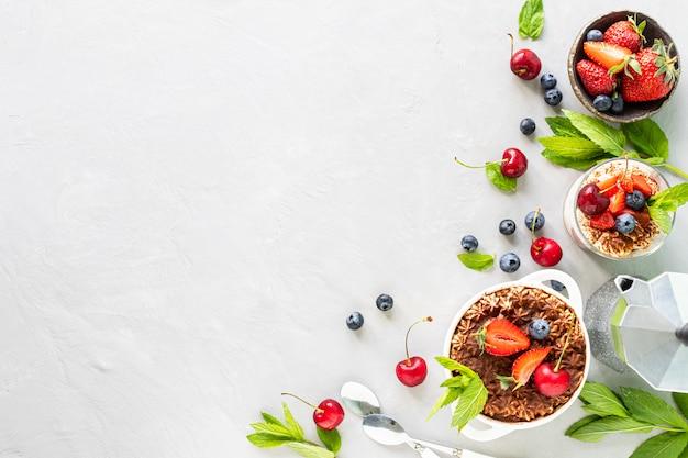티라미수 디저트. 티라미수 준비 재료. 커피, 코코아, 딸기, 흰색 바탕에 민트. 평면도. 텍스트를위한 여유 공간.