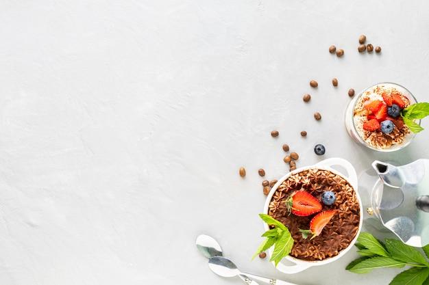 티라미수 디저트. 티라미수 준비를위한 재료. 커피, 코코아, 딸기, 흰색 바탕에 민트. 평면도. 텍스트를위한 여유 공간.