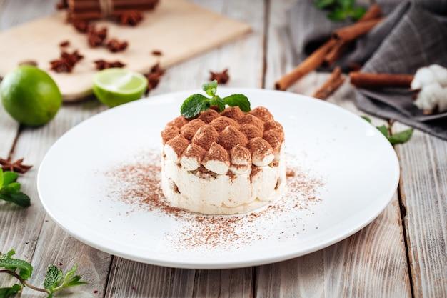 Tiramisu dessert with mint on a white plate