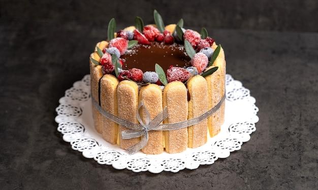 Тирамису сбрызнут шоколадной глазурью и украшен ягодами
