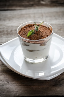 Tiramisu in the glass on the wooden table