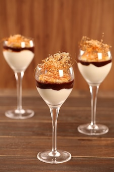 Tiramisu in the glass on the wooden table.