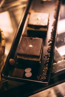 Тирамису - итальянский десерт с ароматом кофе на черном подносе, готовый к продаже.