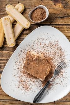 접시에 코코아를 넣은 이탈리아 티라미수 케이크. 나무 배경입니다. 평면도.