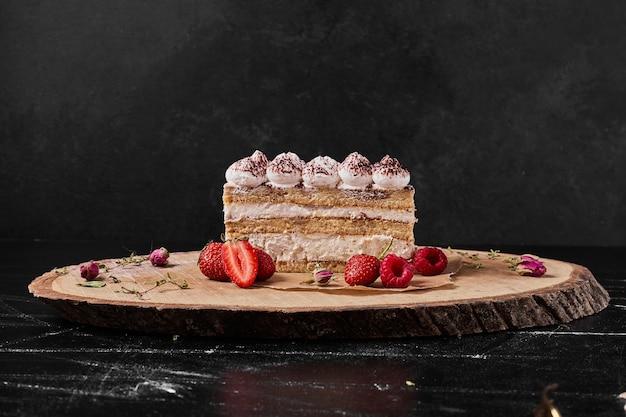 Tiramisu slice on a wooden platter .