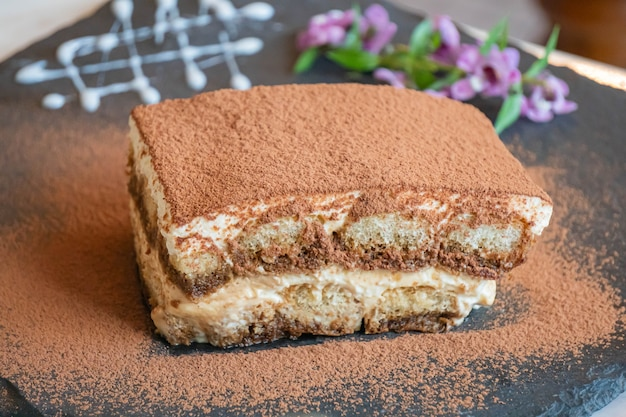 Тирамису. традиционный итальянский десерт на белой тарелке, деревянном фоне. выборочный фокус