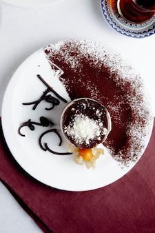 하얀 접시에 코코아 가루와 티라미수
