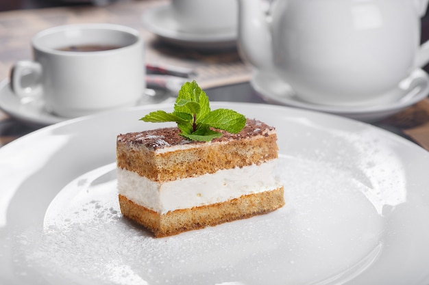 Tiramisu with mint on a white plate