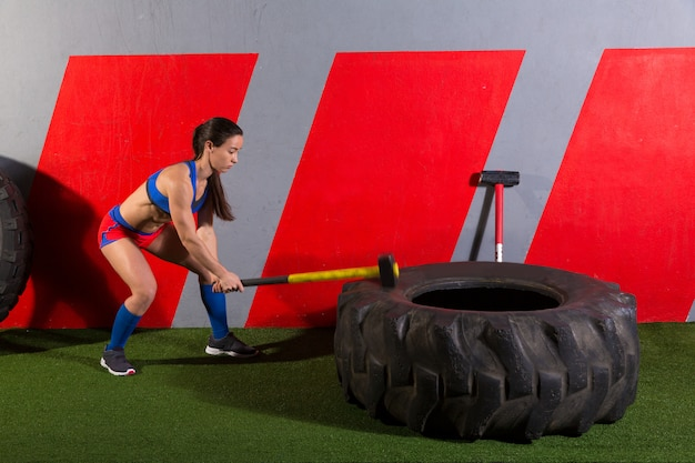Кувалда tire hits женщина тренировки в тренажерном зале