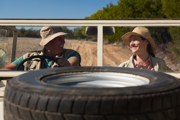 Tire on hood with smiling couple sitting in off road vehicle