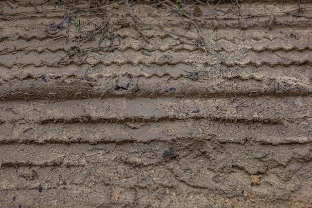 汚れた道の泥の中のタイヤ跡
