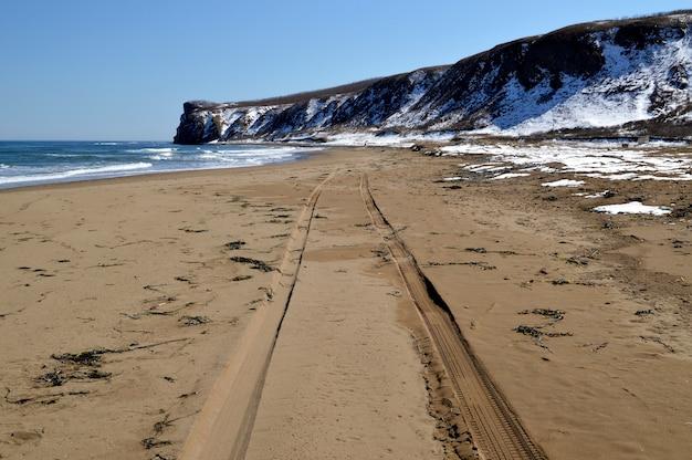 日本海の人けのないビーチの砂にタイヤ跡