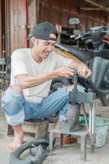 タイヤパッチャーは、オートバイの修理工場で漏れのあるインナーチューブにパッチを当てる前にプレスを保持します