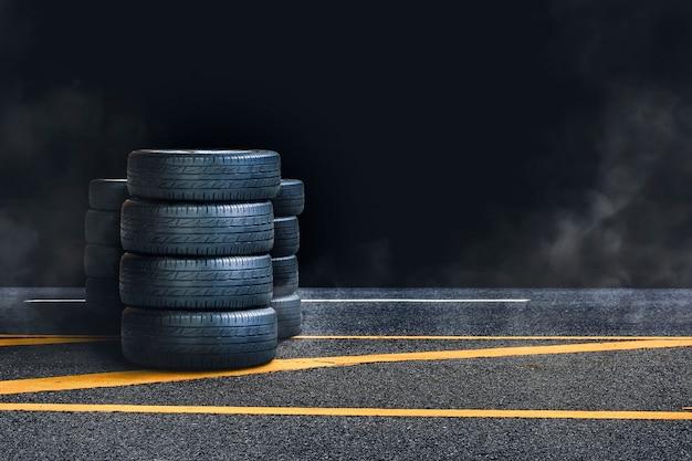 Куча шин на асфальтовой дороге с дымом ночью и черным фоном, копией пространства