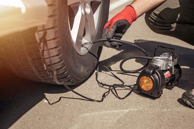 圧力をチェックする男性の手で車のホイールタイヤインフレータを膨らませるタイヤポンプ