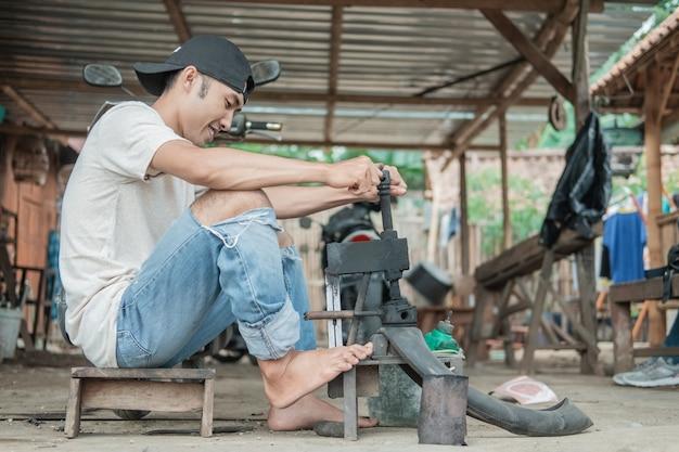 タイヤ修理工は、修理工場でタイヤにパッチを当てている間、足で従来のプレスを保持します