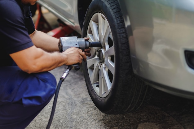 Tire replacement concept. mechanic using electric screwdriver wrench in garage