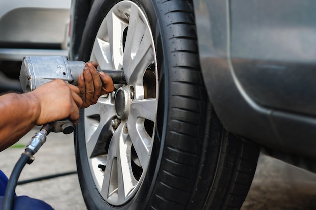 Tire replacement concept. mechanic using electric screwdriver wrench for wheel nuts in garage. car maintenance and services