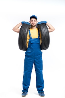 Tire service worker in blue uniform holds car tyres in hands, white background, repairman, wheel mounting