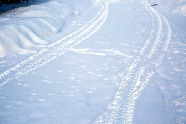 눈 덮인 도로에 타이어 트랙. 눈이 제거되지 않은 겨울 도로. 운전하기 어렵습니다. 마을 시골길