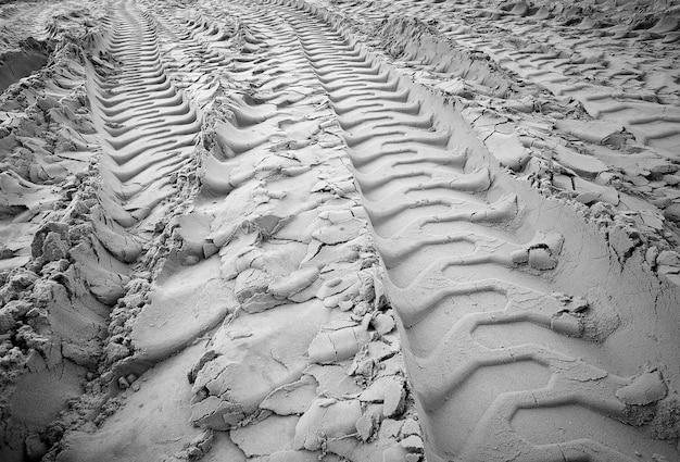 砂の上のタイヤ跡。砂の上の車輪の痕跡。黒と白。